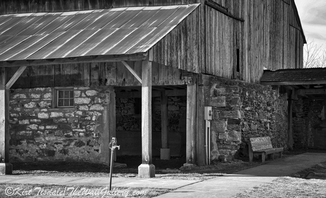 """""""Farm Water Pump"""" is a black and white art print of an old manual water pump next to a barn. The barn is located near the Amana Colonies in Eastern Iowa just south of Cedar Rapids. The architecture of the barn and stables is what caught my eye. I took a number of shots around the property and then I saw this water pump. I framed it against one of the stalls and rock walls of the barn. I like this in black and white because the texture and elements of the barn with the water pump become center stage and don't get lost in colors. The usage of black and white photography as a wall art print lends itself to many different types of interior design, from contemporary to traditional. I think what dictates the look is the subject matter of the photograph and the manner in which it is framed and matted."""