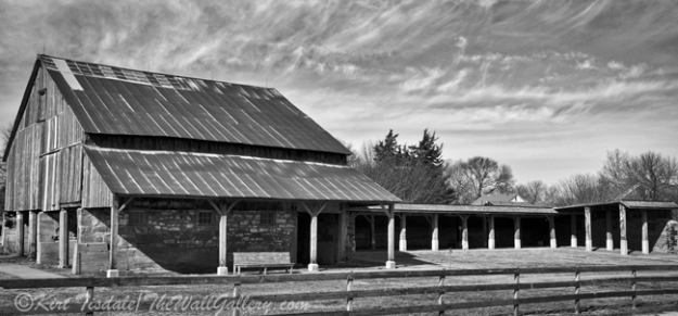 """Barn and Stables"" is a black and white art print of a large barn and stables. The barn is located near the Amana Colonies in Eastern Iowa just south of Cedar Rapids. The architecture of the barn and stables is what caught my eye. The time of year was February, so mid-winter with no leaves on the trees. Because of the barren aspect of the trees, I decided to look at this capture in black and white. The monochrome approach captured the mood of the day at this time of year. The usage of black and white photography as a wall art print lends itself to many different types of interior design, from contemporary to traditional. I think what dictates the look is the subject matter of the photograph and the manner in which it is framed and matted."