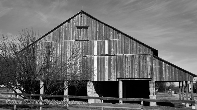 """""""A-Frame Barn"""" is a black and white art print of an a-frame barn. The barn is located near the Amana Colonies in Eastern Iowa just south of Cedar Rapids. The architecture of the roof line and the stalls lining the bottom of the barn is what caught my eye. The time of year was February, so mid-winter with no leaves on the trees. Because of the barren aspect of the trees, I decided to look at this capture in black and white. The monochrome approach captured the mood of the day at this time of year. The usage of black and white photography as a wall art print lends itself to many different types of interior design, from contemporary to traditional. I think what dictates the look is the subject matter of the photograph and the manner in which it is framed and matted."""