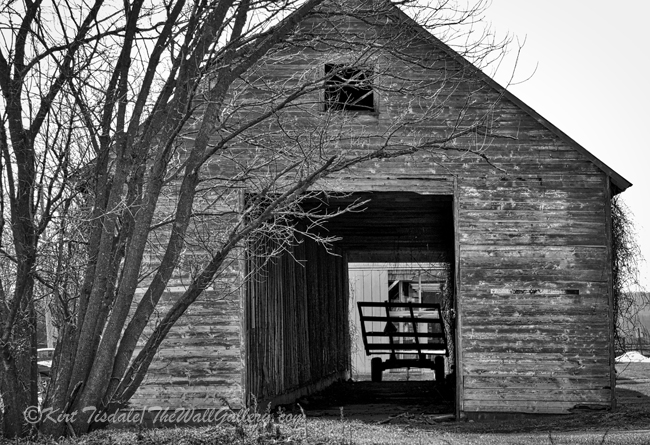 """""""Hay Wagon in Barn"""" is a black and white art print of a hay wagon in a barn. The barn is located near the Amana Colonies in Eastern Iowa just south of Cedar Rapids. The design of the barn is what caught my eye with the center opened up for a hay wagon to pass through. The time of year was February, so mid-winter with no leaves on the trees. Because of the barren aspect of the trees, I decided to look at this capture in black and white. The monochrome approach captured the mood of the day at this time of year. The usage of black and white photography as a wall art print lends itself to many different types of interior design, from contemporary to traditional. I think what dictates the look is the subject matter of the photograph and the manner in which it is framed and matted."""